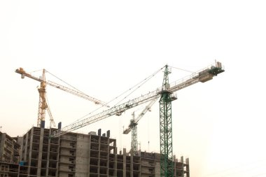 Construction site background with cranes and new multistorey building