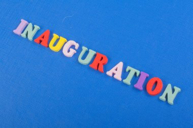 Iinauguration . English word on blue background composed from colorful abc alphabet block wooden letters, copy space for ad text. Learning english concept.