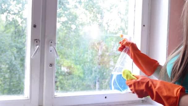 žena v žluté rukavici čistící okno