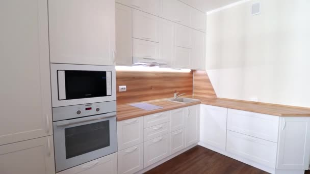 Detaily moderní lehké kuchyně v pohybu. Pohled na světlou kuchyň. Kuchyně. Pohyb ve videu Kuchyně je bílá s dřevěnou deskou. Rusko, Petrohrad, interiér