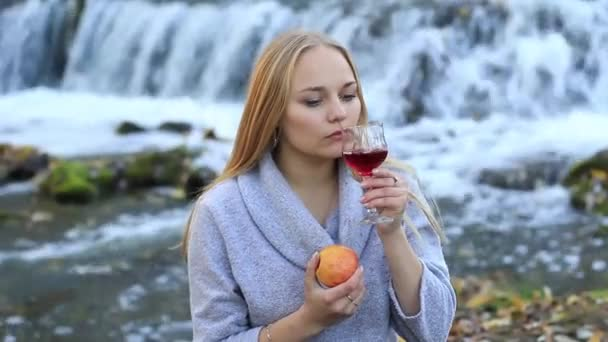 girl tasting wine and eating an apple