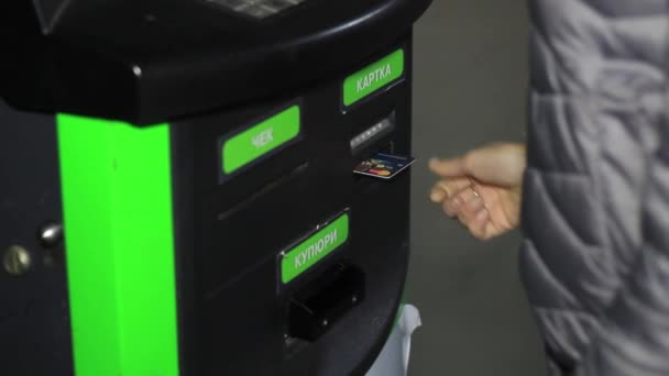 girl at an ATM uses a card