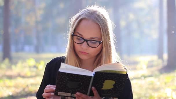 lány olvas egy könyvet az erdőben