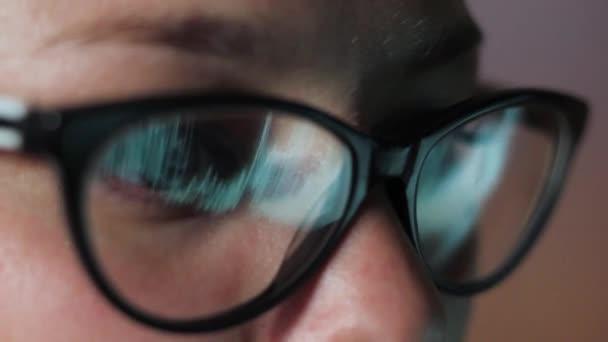 egy szemüveges lány szeme, a monitor közelről