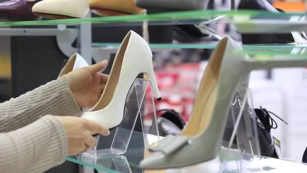 be0f205089 Mani femminili scegliere scarpe con i tacchi in store– filmato stock