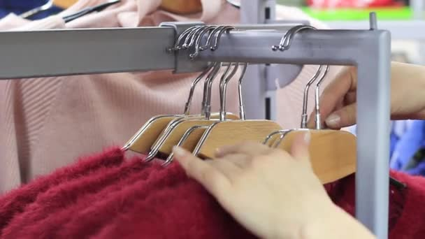 Žena si vybírá pastelové teplé svetry cozy na ramínkách v úložišti