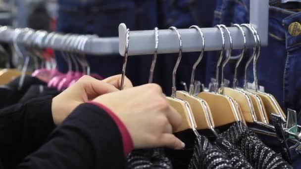 Žena v rukou touch ramínko s oblečení v butiku.