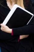 Porträt eines süßen traurigen Mädchens mit digitalem Tablet