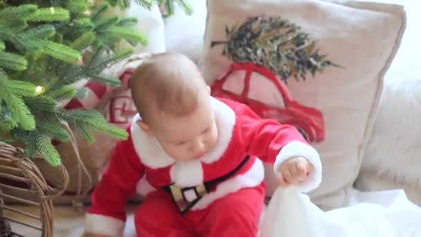 Kleines Baby sitzt auf dem Boden im Zimmer vor einem geschmückten Weihnachtsbaum