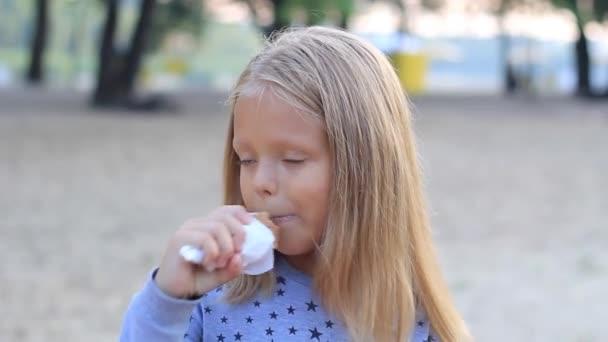 malá holčička v parku jí zmrzlinový kužel zblízka