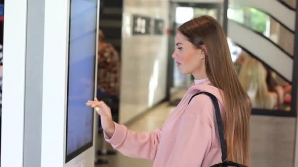 Žena objednává jídlo v dotykové obrazovce terminálu s elektronickým menu ve fast-foodu