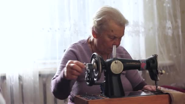 grandmother sew fabric clothes with a sewing machine