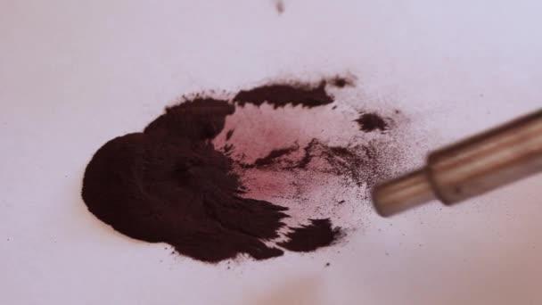 Magnetický kovový kartáč sbírá magnetický prášek z listu bílého papíru zblízka.