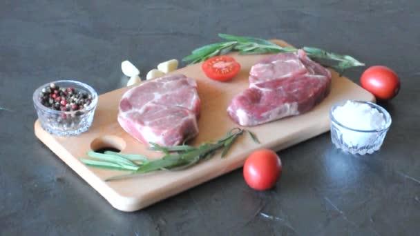 Nyers sertéshús rozmaringgal, fokhagymával, sóval, borssal és paradicsommal fa vágódeszkán