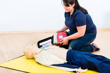 First aider trainee learning revival with defibrillator