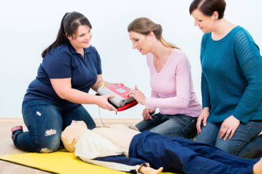 First aid trainees learning to use defibrillator for reanimation