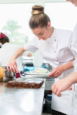 Confectioner putting chocolate as frosting on cake