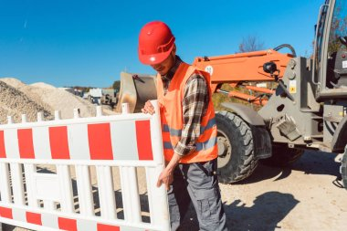 Worker setting up earthworks construction site