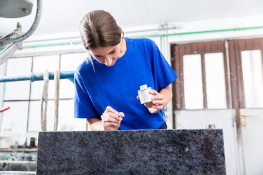 Female Stonemason applying inscription on tombstone