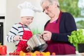 Fotografie Granny cooking together with her grandson