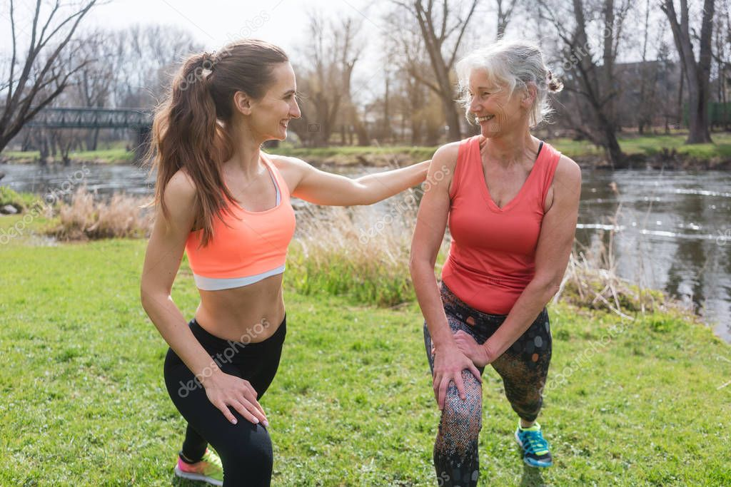 Senior woman with personal fitness trainer doing sport on meadow