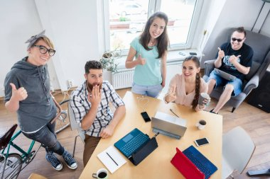 Young cheerful people showing thumbs up for co-working