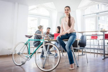 Confident young woman sitting on a desk near her commuter bike
