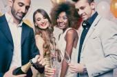 Fotografie Man opening champagne bottle on celebration in club