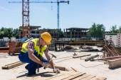 Fotografie Seitenansicht eines jungen Arbeiters hämmern einen Nagel ins Holz während der Arbeit