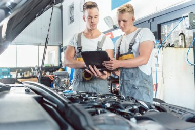 Experienced auto mechanic using a laptop for scanning engine errors