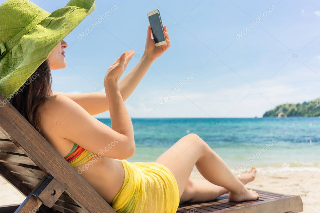 Attractive young woman sending a love message through a selfie on the beach
