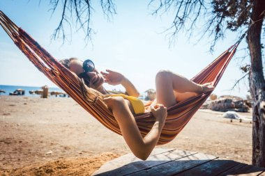 Woman lying in hammock close to the beach