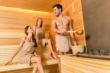 Young and beautiful people smiling while socializing in a wooden sauna