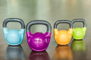 Close-up of four kettlebells of different colors and weights