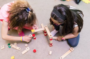 High-angle view of two pre-school girls sharing wooden toy blocks