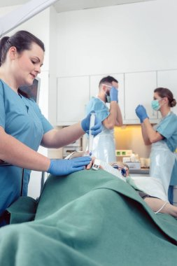 Nurse giving anesthesia to patient waiting for endoscopy