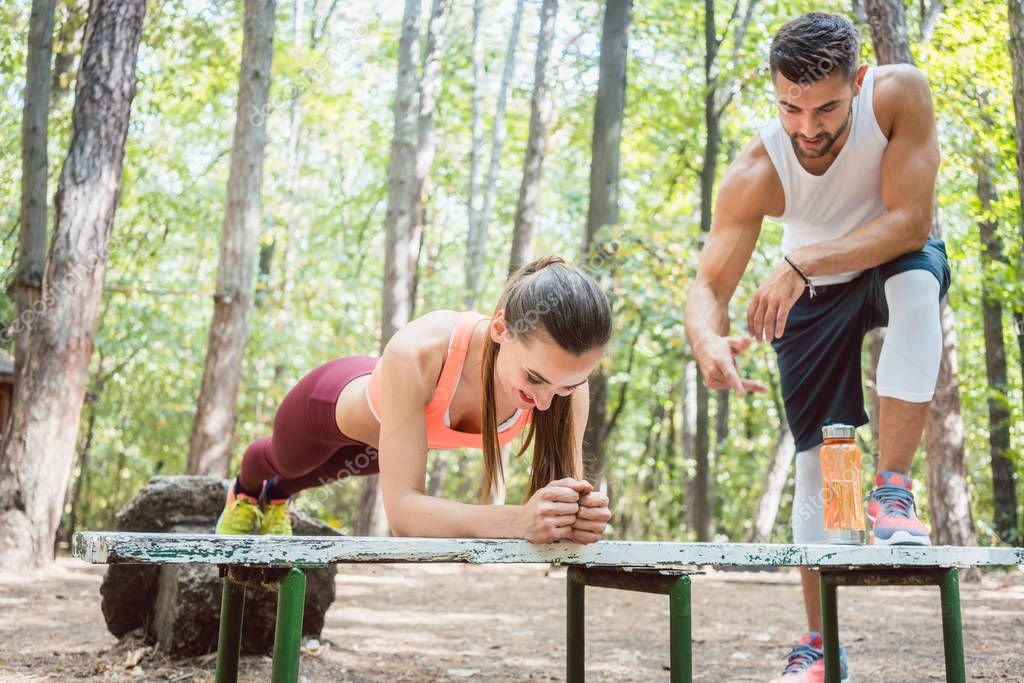 Beautiful woman doing a plank with man watching