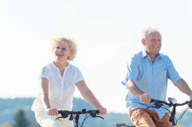 Active elderly couple riding bicycles together in the countryside