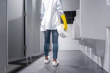 Janitor woman changing paper in public toilet
