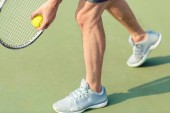 Fotografie Low section of a professional player holding ball and tennis racket