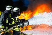 Hasič - velký požár, hašení hasiči stojí s ochranným opotřebení přední stěna ohně