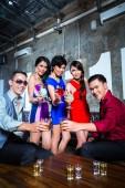 Asijské kumpáni koktejly v nočním klubu
