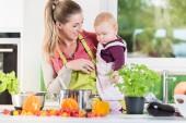 Fotografie Mutter arbeitet in der Küche während des Tragens Kind