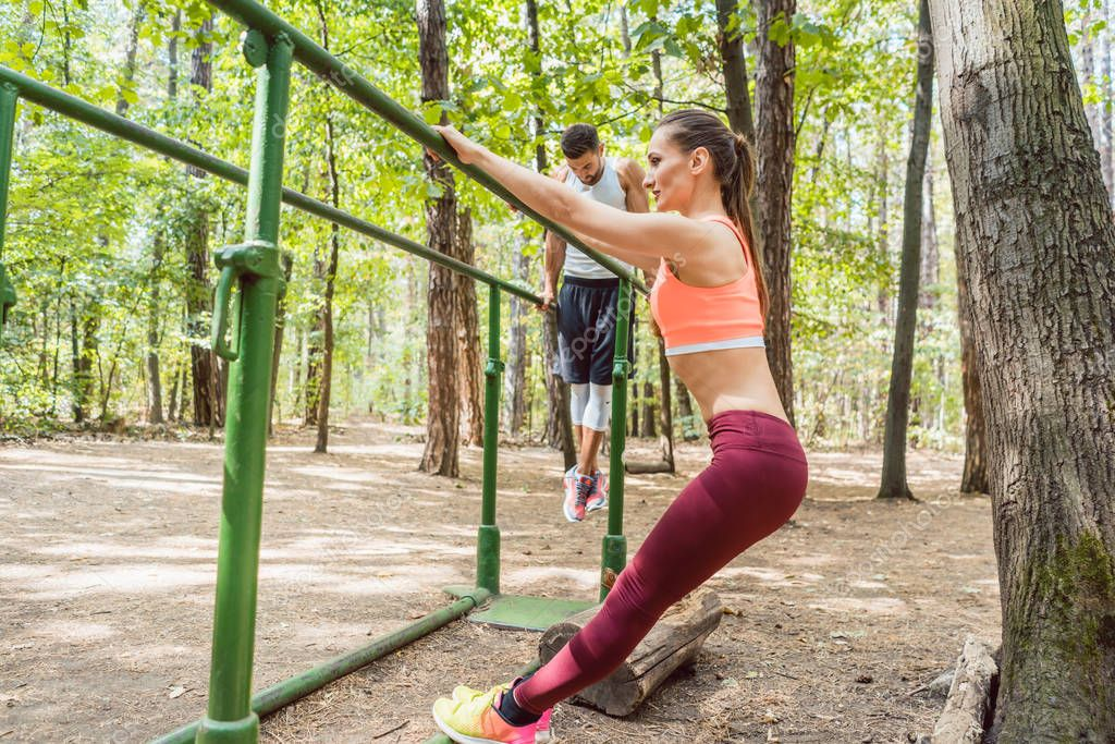 Couple doing full fitness workout in outdoor gym