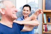 Starší pacient dělá rameno cvičení za pomoci terapeuta