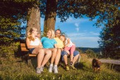 Family resting on bench during a long walk in summer