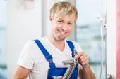 Fotografie Porträt eines fröhlichen Wartung Arbeitnehmers hält einen Wasserhahn