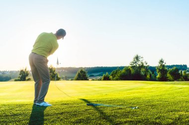 Experienced male golfer hitting the golf ball towards the cup
