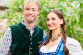 Fotografie Couple posing in Bavarian clothes in beer garden