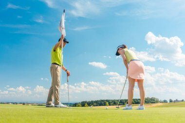 Female golf player ready to hit the ball under the instruction of a golf teacher